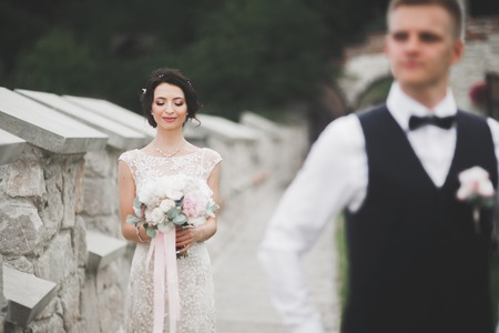 Foto de Stylish couple of happy newlyweds walking in the park on their wedding day with bouquet - Imagen libre de derechos
