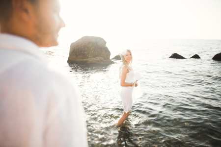 Photo pour Just married wedding couple walking on the beach at sunset. - image libre de droit