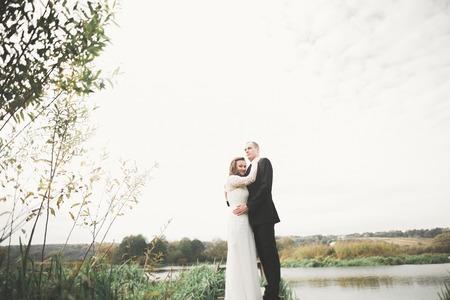Foto de Romantic, fairytale, happy newlywed couple hugging and kissing in a park, trees in background - Imagen libre de derechos