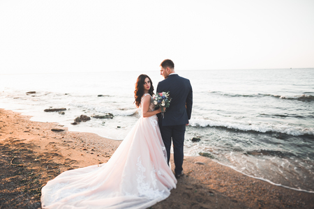 Foto de Wedding couple, groom, bride with bouquet posing near sea and blue sky - Imagen libre de derechos