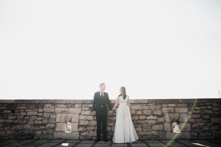 Foto de Beautiful romantic wedding couple of newlyweds hugging near old castle - Imagen libre de derechos