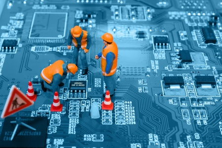 Miniature engineers fixing error on chip of circuit board. Computer repair concept. Close-up view.