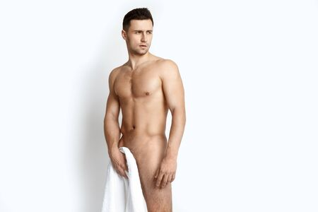 Photo pour Strong stripped muscle male model with white towel on white isolated background - image libre de droit