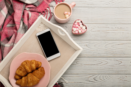 Foto de Knitted pillows and plaid, smartphone, croissants and coffee on a light wooden background. Top view. Flat lay. - Imagen libre de derechos