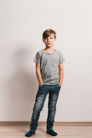 Photo pour a cute boy stands next to white wall, grey t-shirt, blue jeans, hands in pockets - image libre de droit