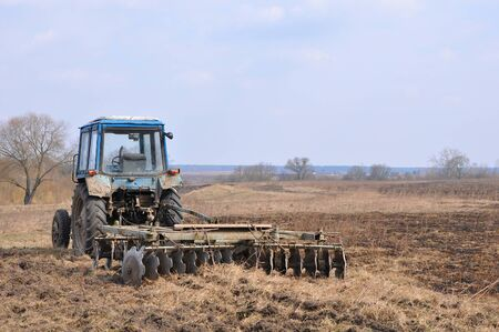 Photo pour Empty blue spattered tractor with rusty harrow on the field in early Spring - image libre de droit