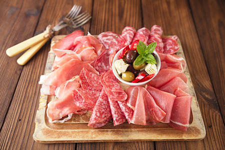 Photo pour antipasti Platter of Cured Meat,   jamon, olives, sausage, salami,  ciabatta and white wine glasses on textured wooden table - image libre de droit