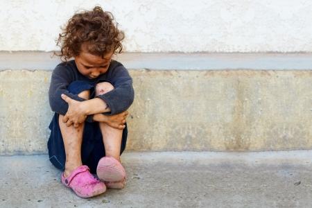 Foto de poor, sad little child girl sitting against the concrete wall - Imagen libre de derechos