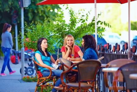 beautiful female friends sitting on cafe terrace