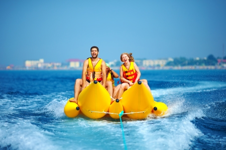 Photo pour happy people having fun on banana boat - image libre de droit