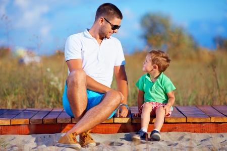 Foto de father and son talking, summer outdoor - Imagen libre de derechos