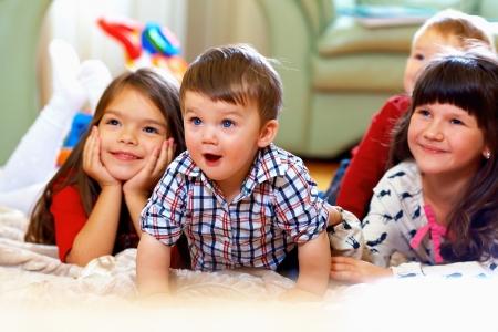 Photo pour group of happy kids watching tv at home - image libre de droit