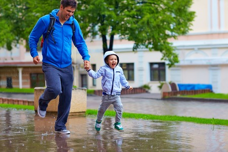 happy father and son running under the rain