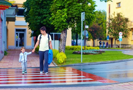 Photo for father and son crossing the city street on crosswalk - Royalty Free Image