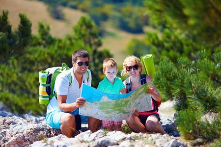 Photo pour happy family in mountains discussing the route - image libre de droit