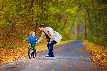 Photo for father teaches son to ride the bicycle - Royalty Free Image