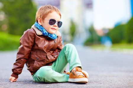 Foto de cute stylish boy in leather jacket sitting on the road - Imagen libre de derechos