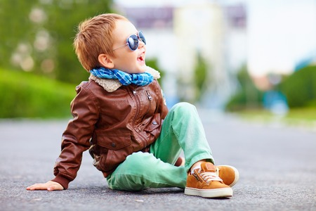 Photo pour happy boy in leather jacket posing on the ground - image libre de droit