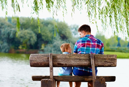 Photo for father and son sitting on the bench near the lake - Royalty Free Image