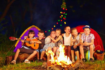 Photo pour happy kids singing songs around camp fire - image libre de droit
