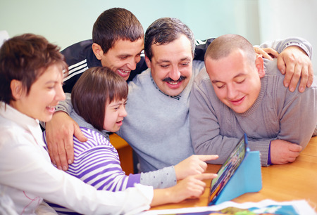 Foto de group of happy people with disability having fun with tablet - Imagen libre de derechos