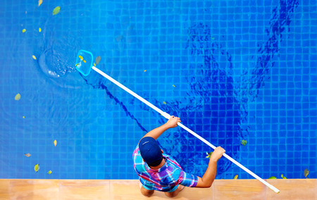 Photo pour young adult man, personnel cleaning the pool from leaves - image libre de droit