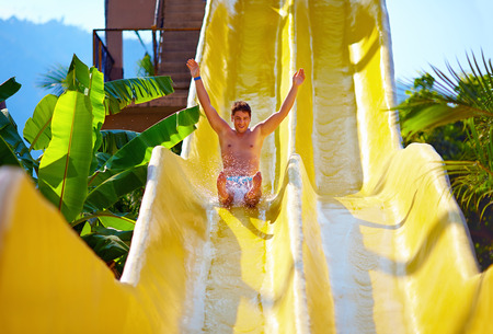 Photo for excited man having fun on water slide in tropical aqua park - Royalty Free Image