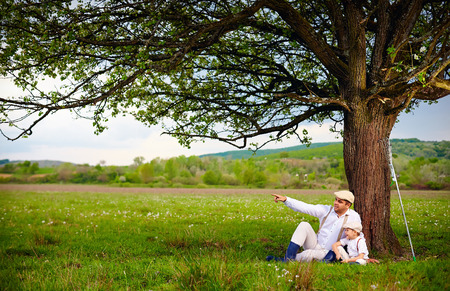 Photo pour Farmer father and son sitting under the tree spring countryside - image libre de droit