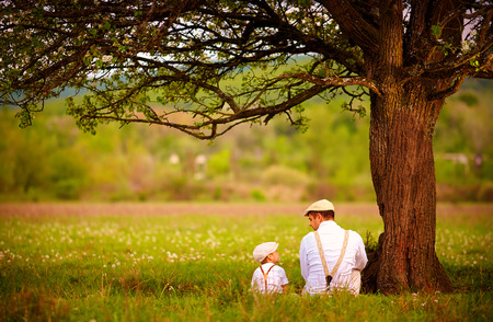 Foto de father and son sitting under the tree on spring lawn - Imagen libre de derechos