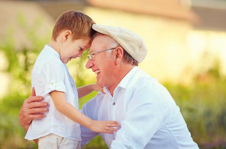 Foto de portrait of happy grandfather and grandson bow their heads - Imagen libre de derechos