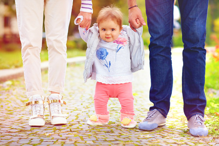 Photo for cute little baby girl on walk with parent, first steps - Royalty Free Image