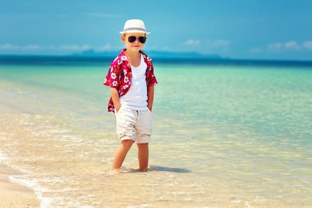 Foto de cute fashionable boy stands in surf on summer beach - Imagen libre de derechos