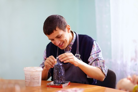 Foto de young adult man with disability engaged in craftsmanship on practical lesson, in rehabilitation center - Imagen libre de derechos
