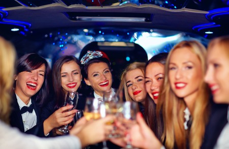 Photo for group of happy elegant women clinking glasses in limousine hen party - Royalty Free Image