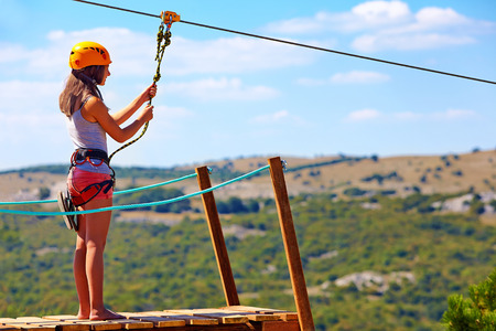 Photo pour young woman are ready to descend on zipline in mountain extreme sport - image libre de droit
