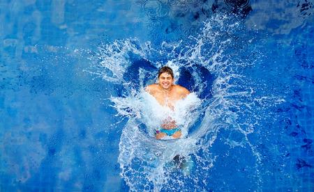 Photo pour man jumping in pool huge splash top view - image libre de droit