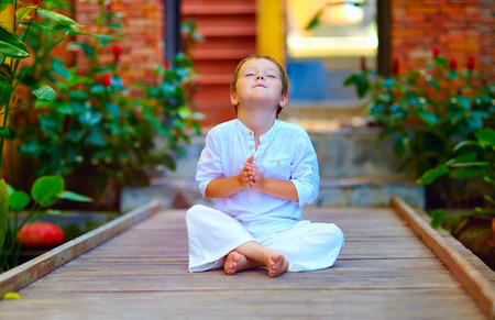 Photo pour cute boy trying to find inner balance in meditation - image libre de droit