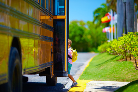 Foto de young boy, kid getting on the schoolbus, ready to go to school - Imagen libre de derechos