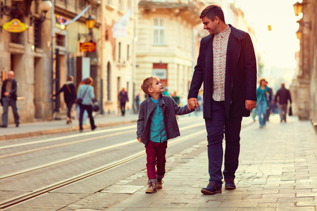 Foto de fashionable father and son walking in old city street - Imagen libre de derechos
