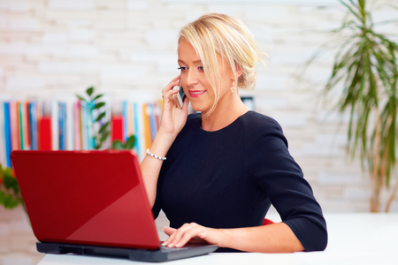 Photo pour attractive business woman talking on the phone in office - image libre de droit