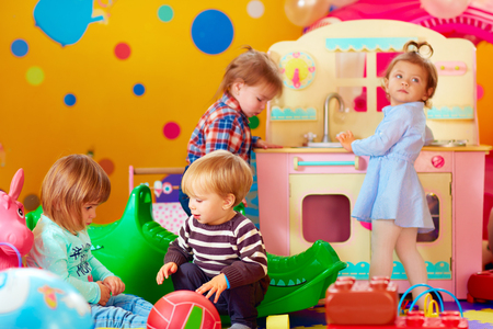 Foto de cute little kids playing with toys in nursery group of kindergarten - Imagen libre de derechos