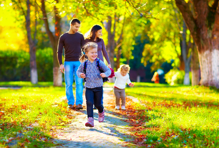 Photo for happy young girl running in autumn park with her family on background - Royalty Free Image