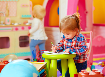 Foto de cute little girl drawing with pencil in kindergarten - Imagen libre de derechos
