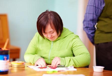Foto de young adult woman with disability engaged in craftsmanship in rehabilitation center - Imagen libre de derechos