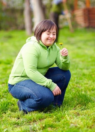 Foto de young adult woman with disability enjoying nature in spring garden - Imagen libre de derechos