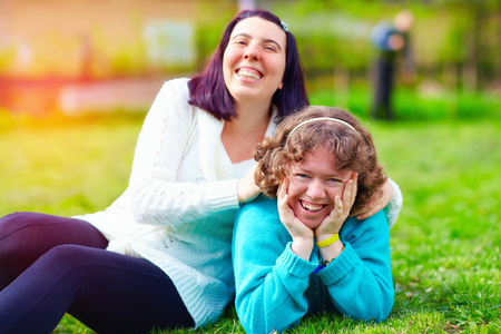 Foto de portrait of happy women with disability on spring lawn - Imagen libre de derechos
