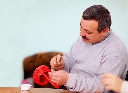 Foto de young adult man engaged in craft work in rehabilitation center - Imagen libre de derechos