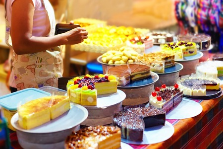 Photo pour sweet tasty cakes  on display at pastry stall, at night street market - image libre de droit
