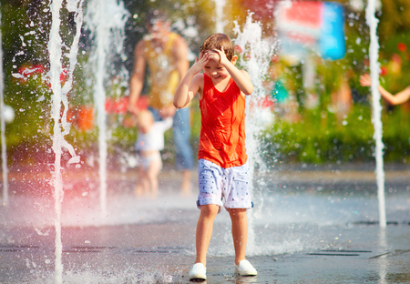 Photo for excited boy having fun between water jets, in fountain. Summer in the city - Royalty Free Image