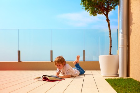 Photo pour young boy, kid reading book on rooftop terrace, while lying down on decking - image libre de droit